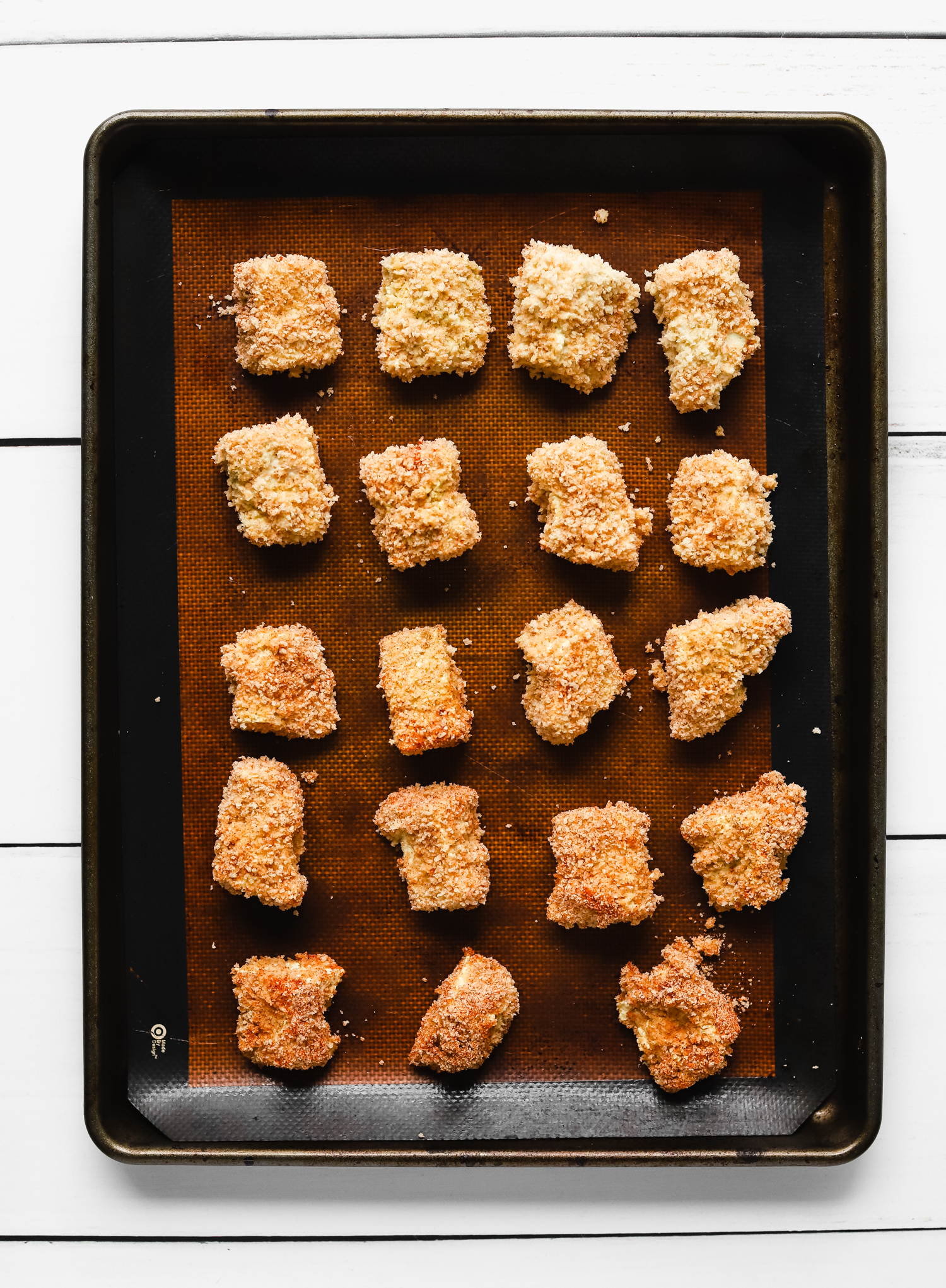 Unbaked breaded tofu chicken nuggets on a baking tray lined with a reusable silicone mat.