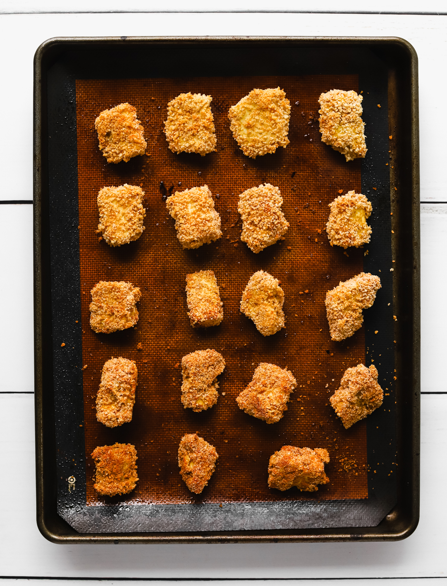 Baked breaded tofu chicken nuggets on a baking tray lined with a reusable silicone mat.