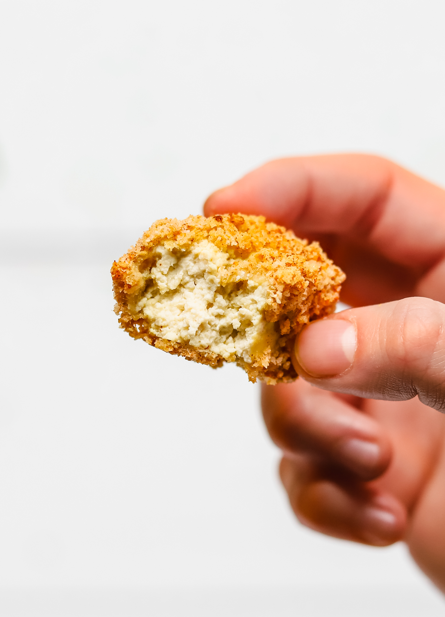 Bite taken out of a vegan chicken nugget, revealing a chewy texture created by using tofu that has been frozen and thawed.