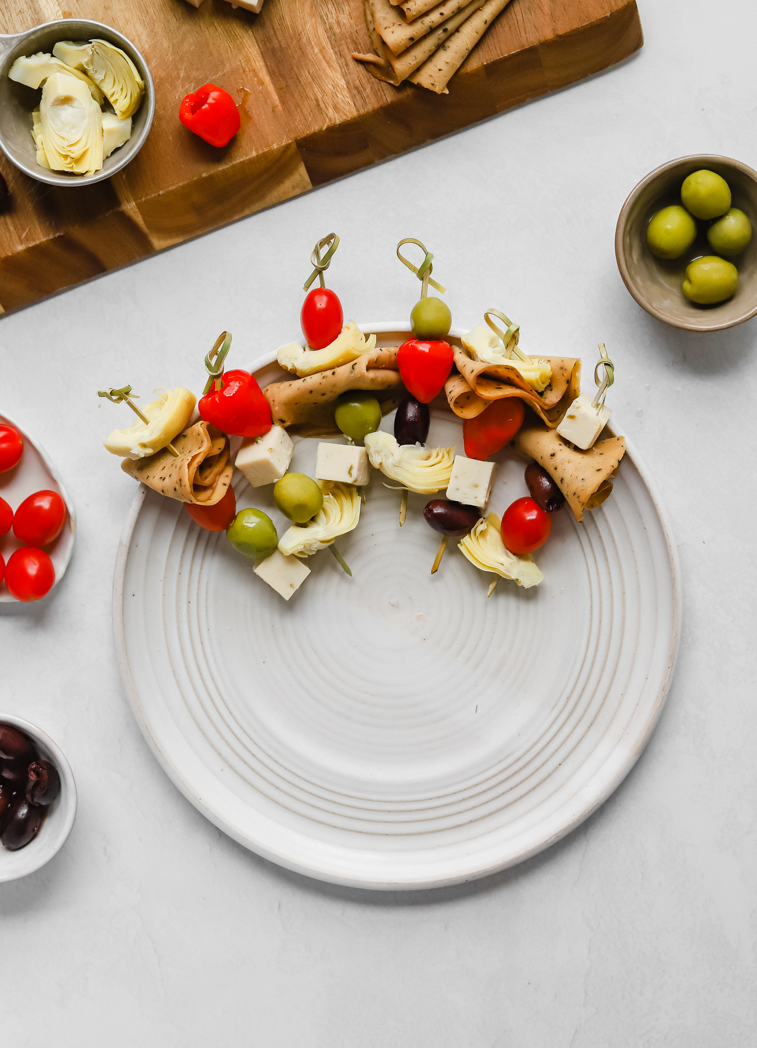Skewers with olives, tomatoes, artichoke hearts, peppers, vegan deli meat, and vegan cheese on a white plate.