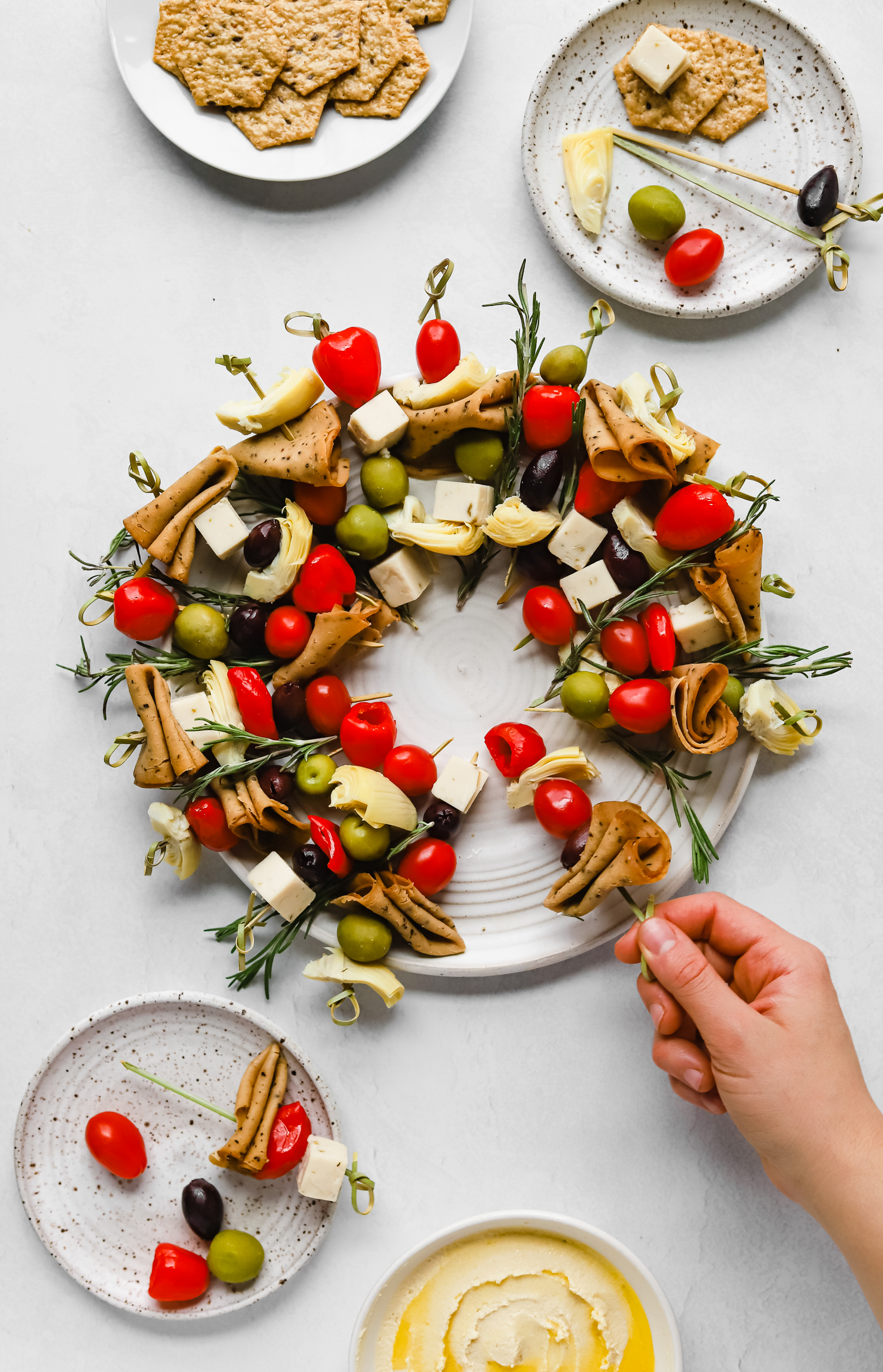 Hand grabbing a skewer from the vegan charcuterie Christmas wreath snack board, surrounded by small plates, crackers, and hummus.