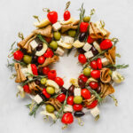 Vegan charcuterie Christmas wreath snack board on a large white serving plate.