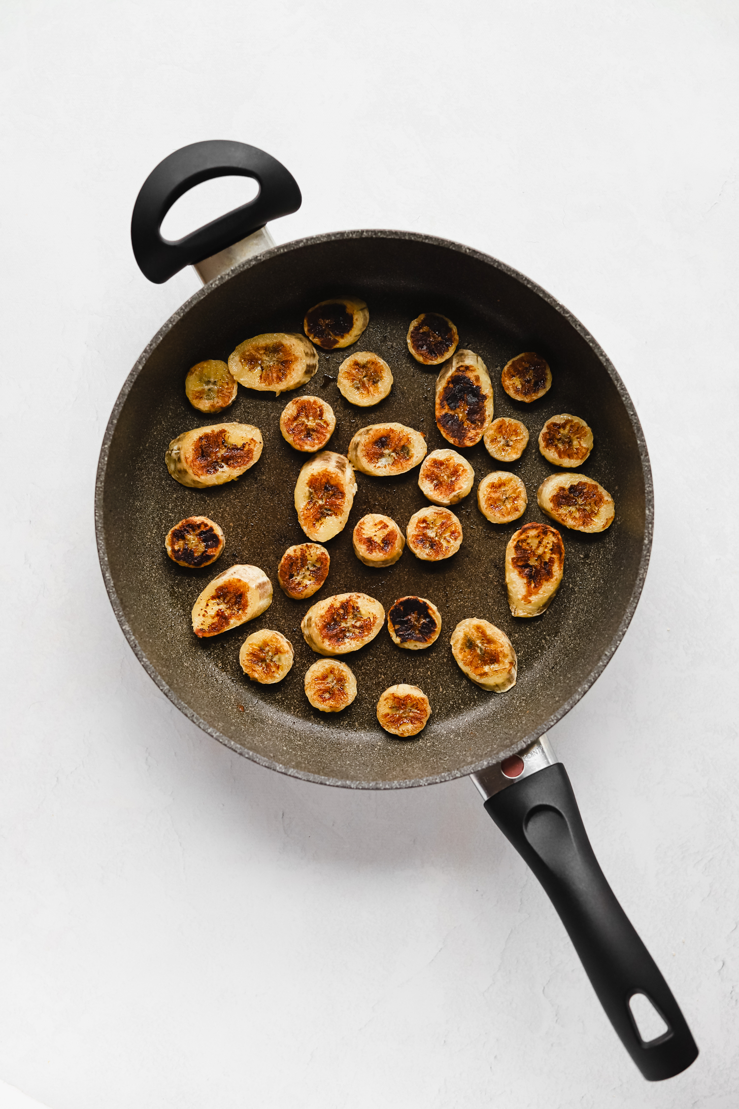 Caramelizing banana slices in coconut oil in a large pan
