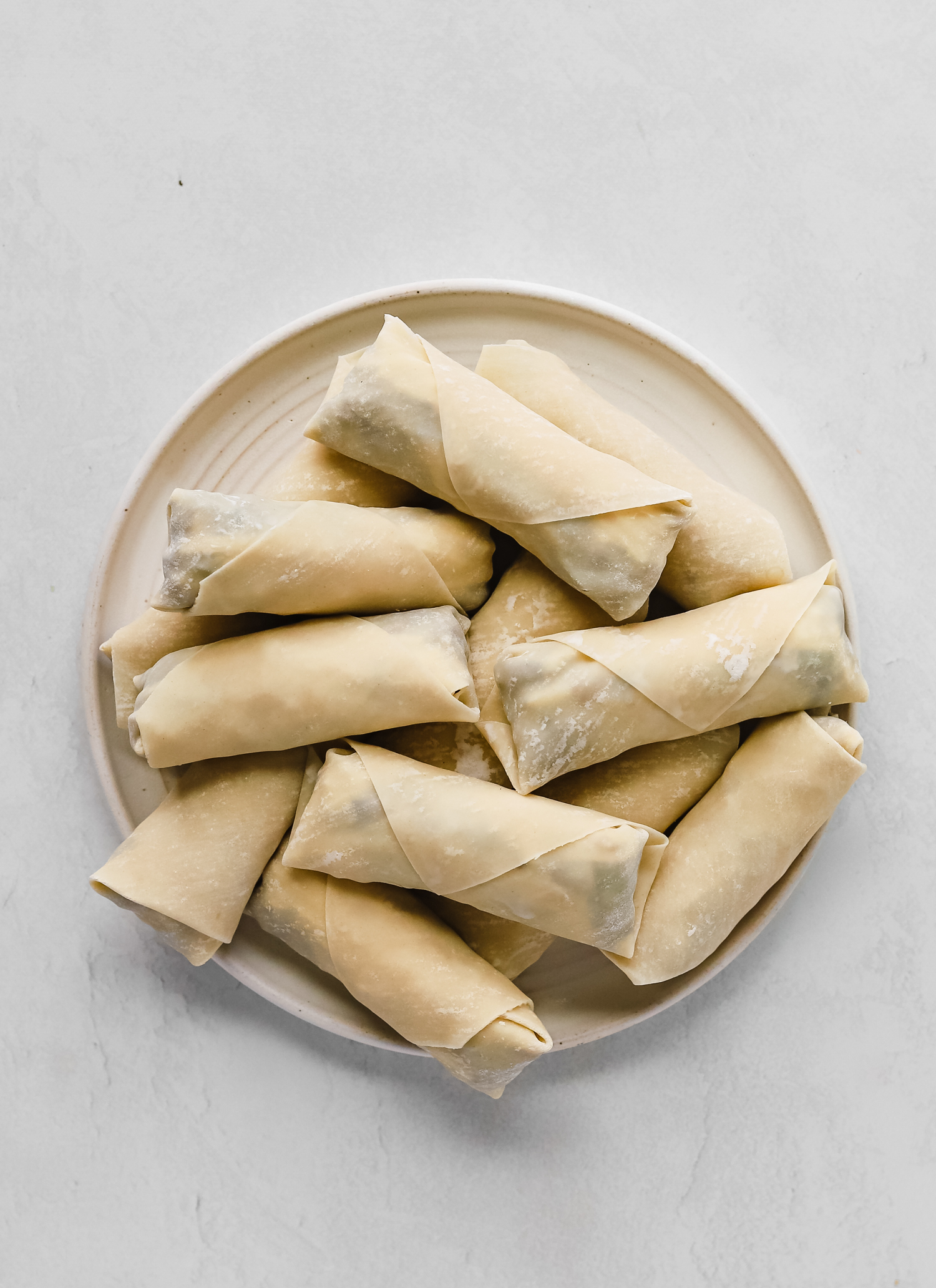 Freshly wrapped unbaked philly cheesesteak egg rolls on a white plate
