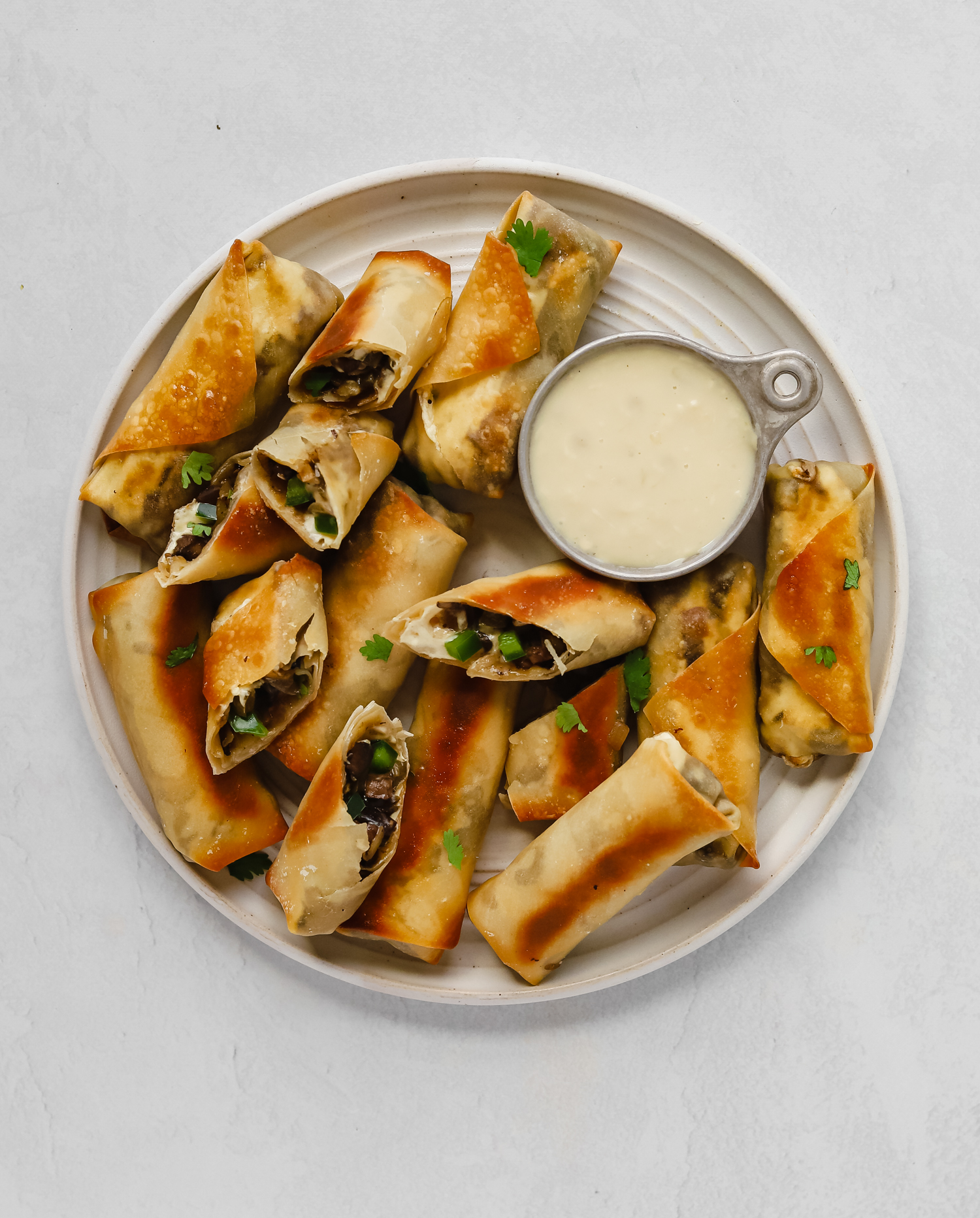 A plate of vegan philly cheesesteak egg rolls with a cheese dipping sauce on a white plate