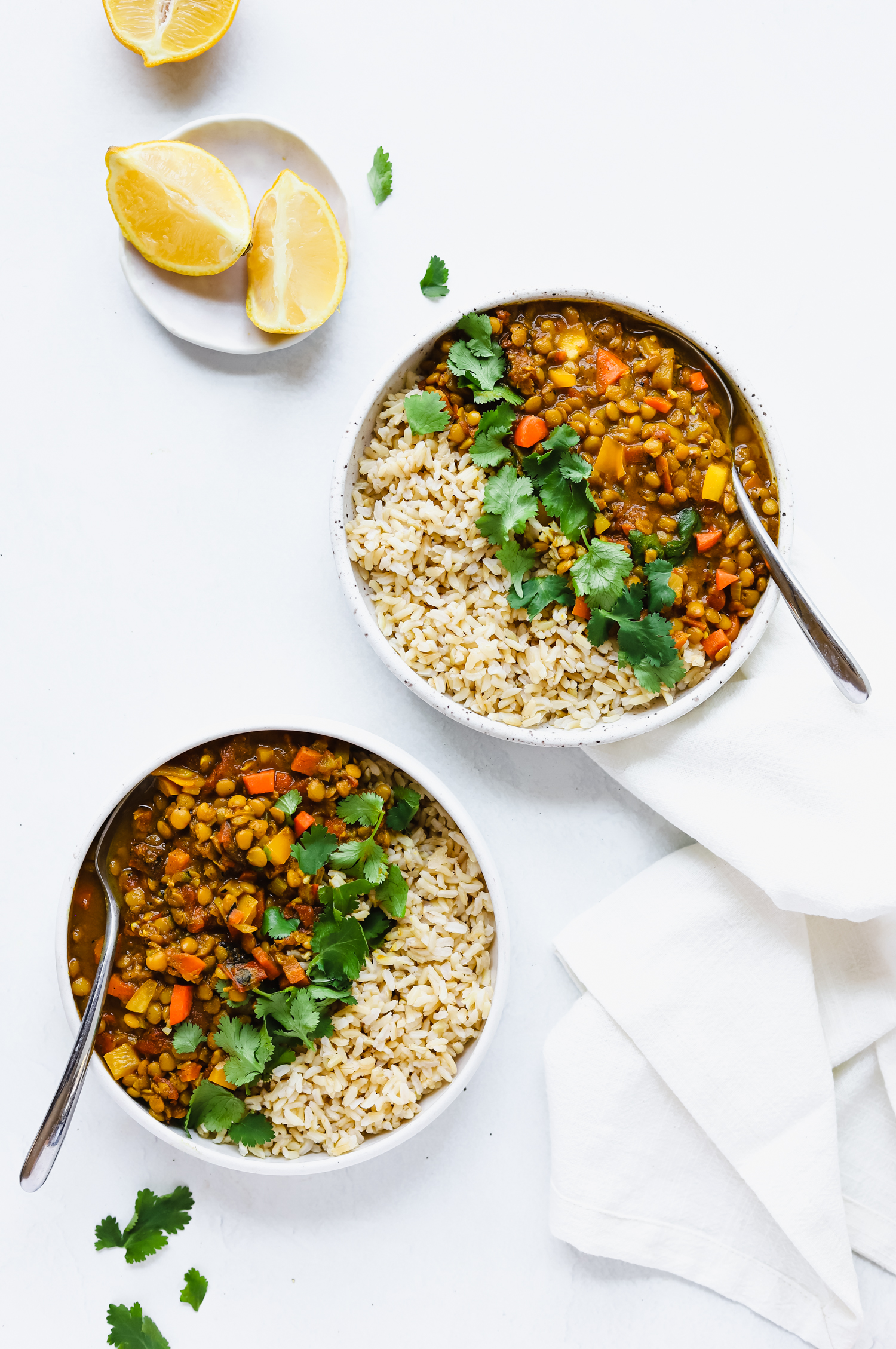 Two bowls of vegetarian almond milk lentil curry with rice, cilantro, and lemons.