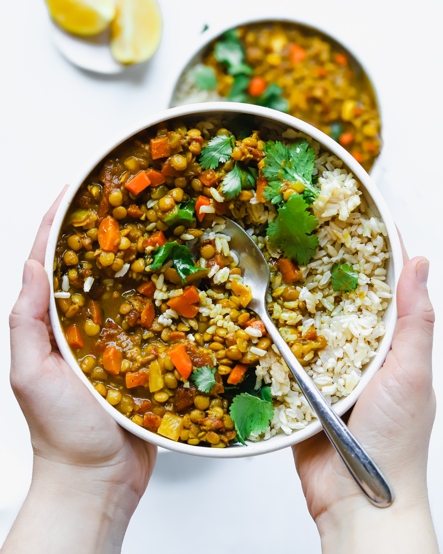 Holding a warm, comforting bowl of lentil curry, rice, and cilantro.