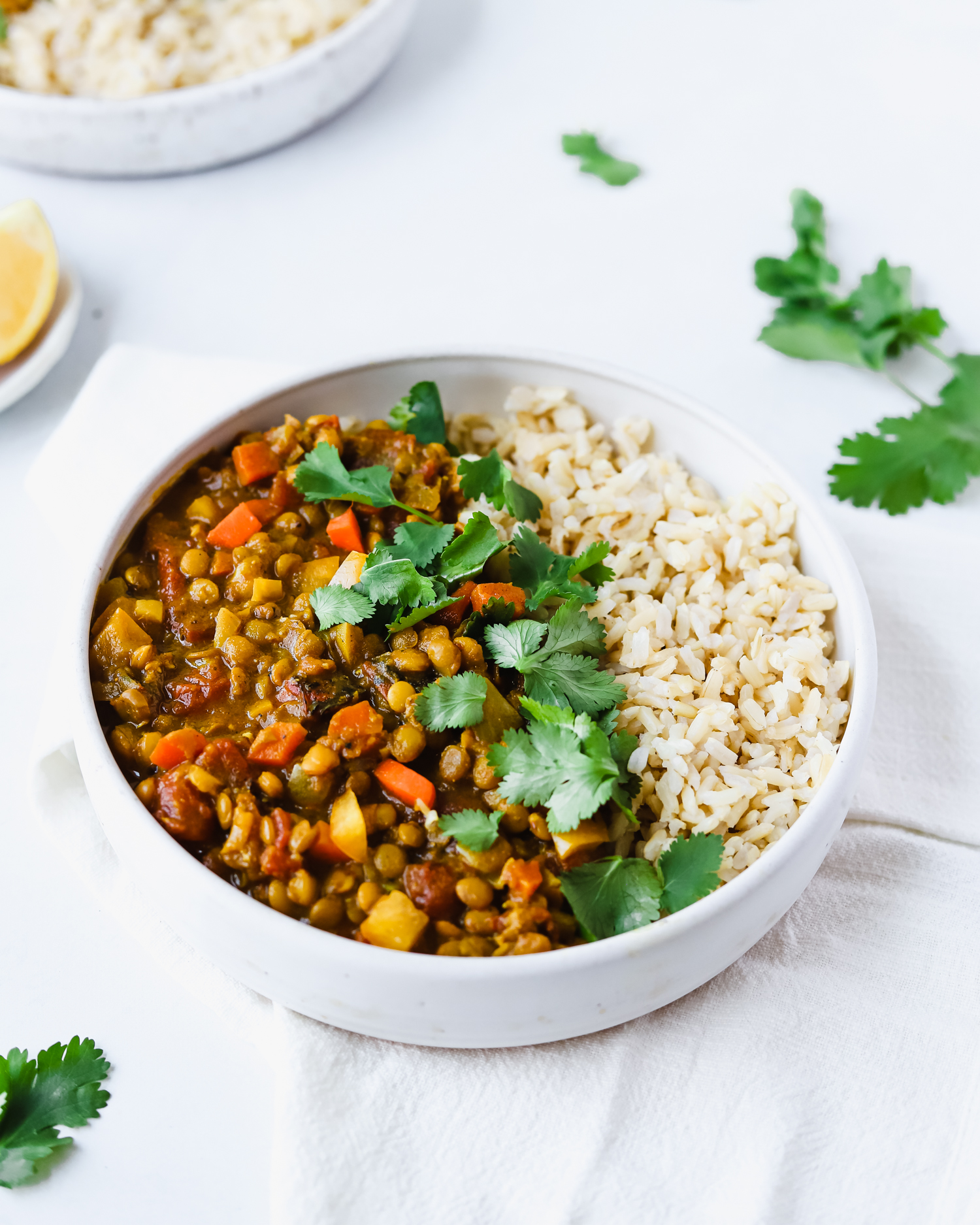 A white bowl of easy vegan almond milk lentil curry served with rice and fresh cilantro.