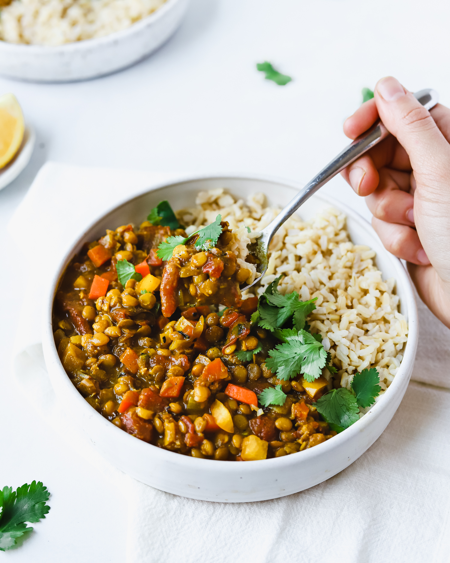 Eating a bowl of lentil curry with a spoon.