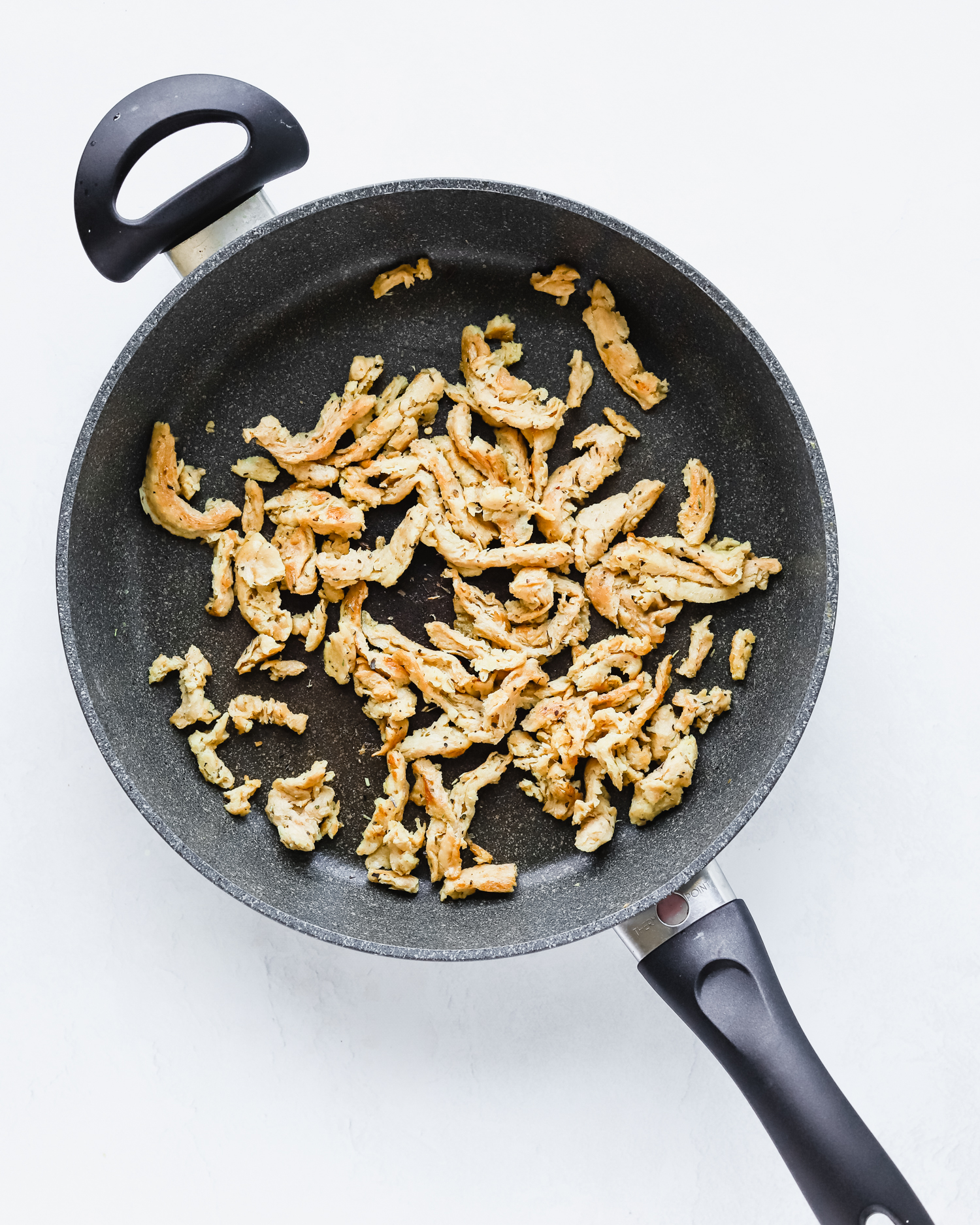 Soy curls sautéing in a pan with italian seasoning.