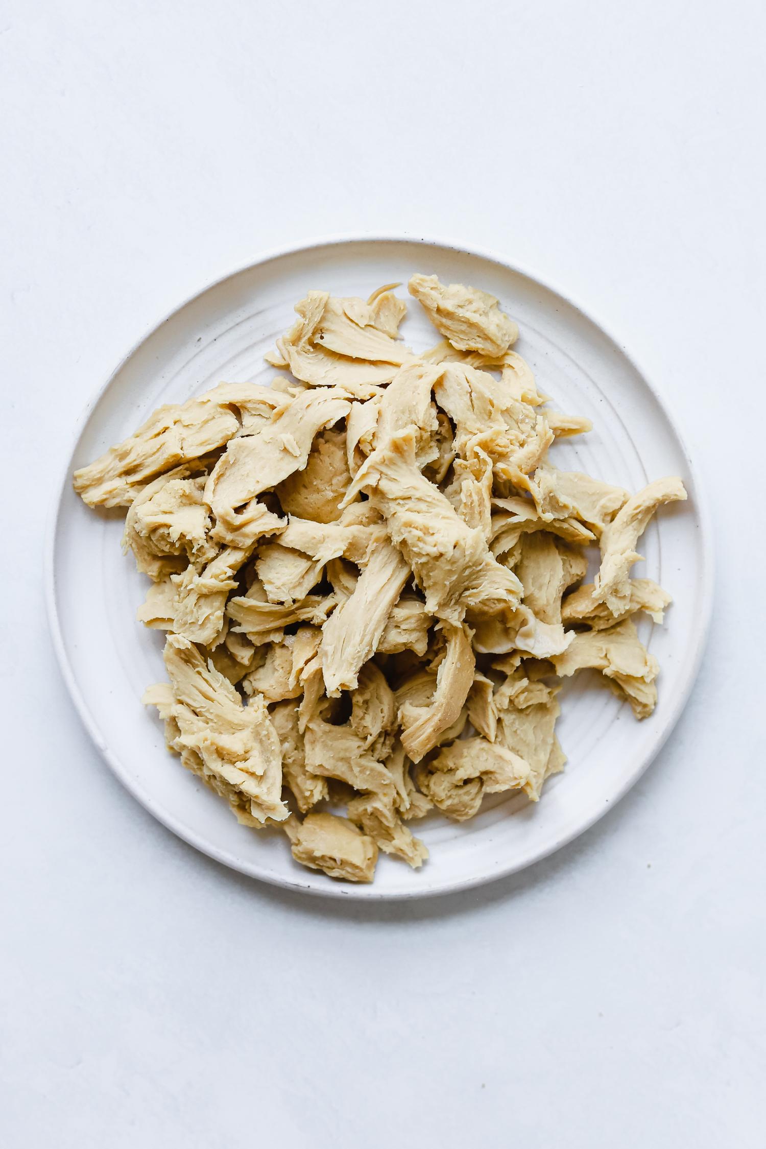 Seitan chicken shreds on a white plate.