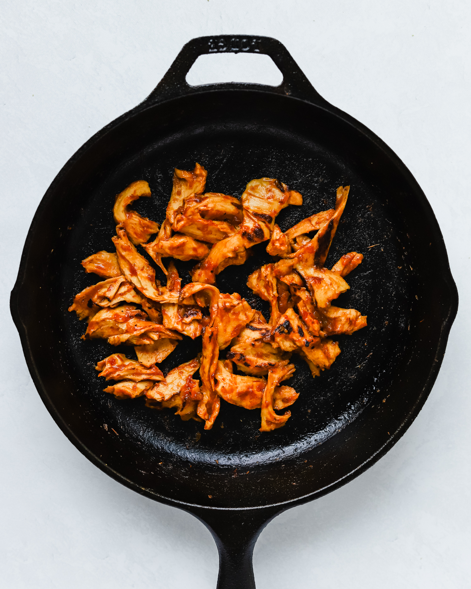 Seitan chicken shreds covered with BBQ sauce in a cast iron pan.