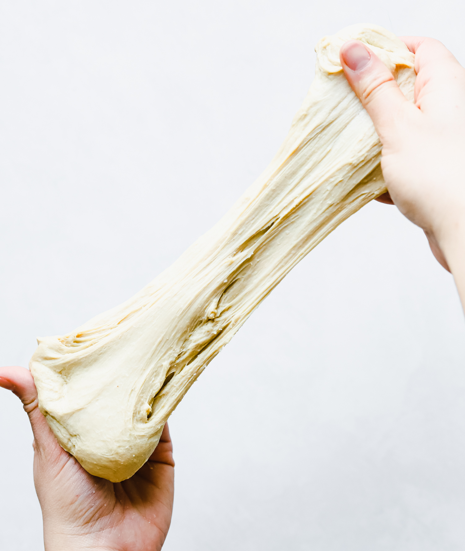 Stretching kneaded seitan dough, showing gluten formation.