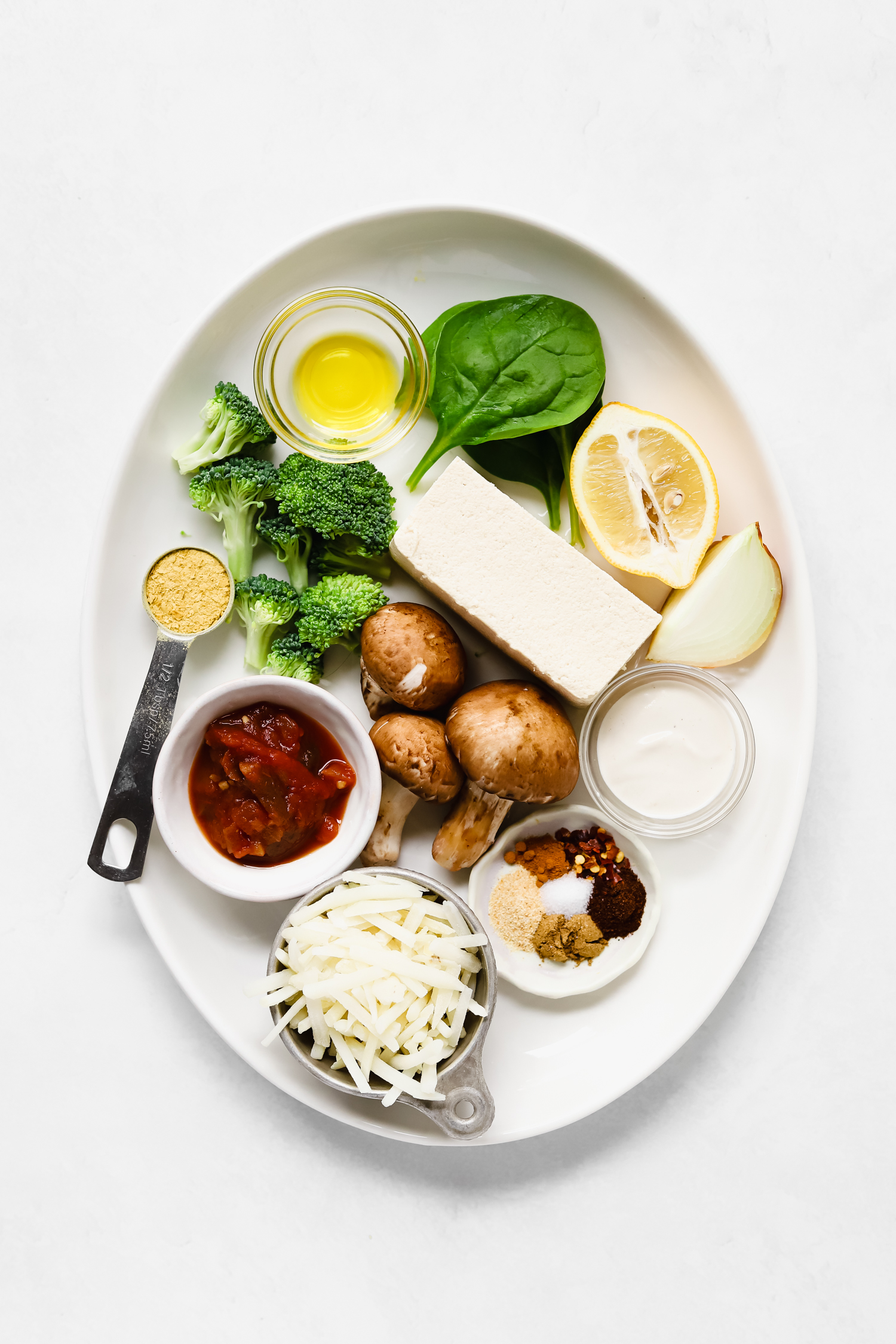 Ingredients for tofu scramble on an oval white platter.