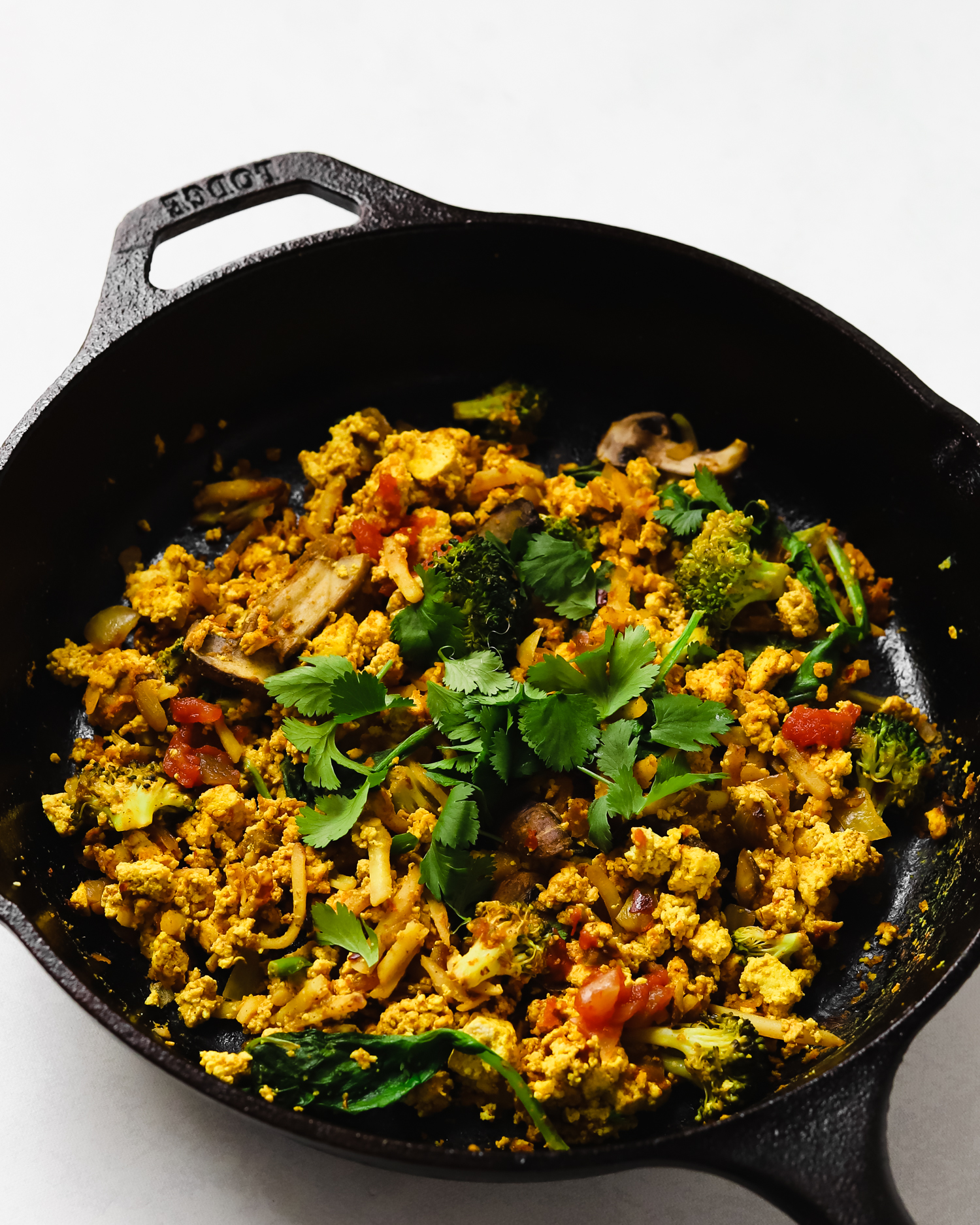 Delicious vegan tofu scramble with vegetables topped with fresh cilantro in a black cast iron skillet.